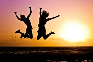 夕日の前で飛び跳ねる二人のシルエット画像