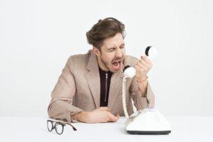 電話で怒る人の画像