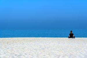 白い砂浜に一人座る画像